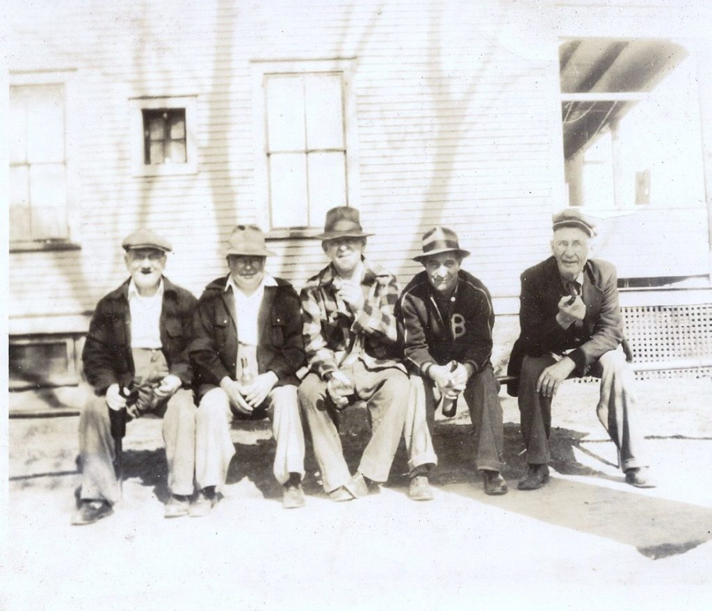 In the foreground there are five older white men sitting on a bench. In the background in front of a building. The photo is black and white.
